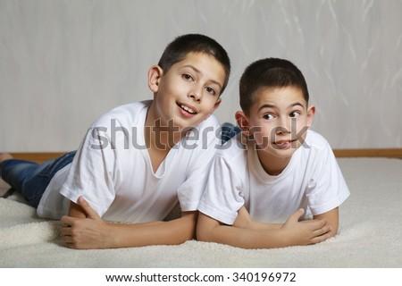 photo of cheerful brothers lying on floor - stock photo