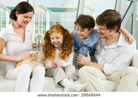 Photo of cheerful children and their father looking at cat on female?s knees during home rest