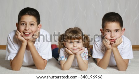 photo of cheerful children lying on floor together - stock photo