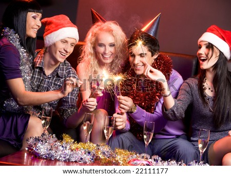 Photo of cheerful friends laughing and having fun at Christmas party