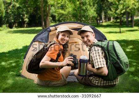 Photo of cheerful girl and guy sitting on green grass by tent and looking at camera with smiles - stock photo