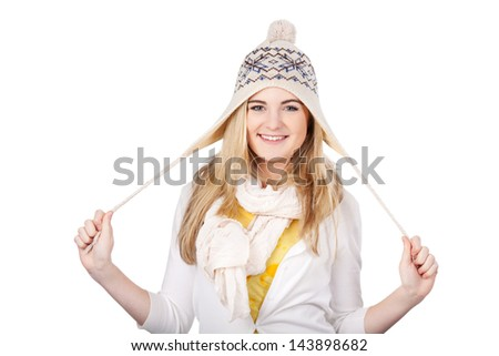 Photo of cheerful teenage girl playing with her woolen cap, isolated on white background. - stock photo