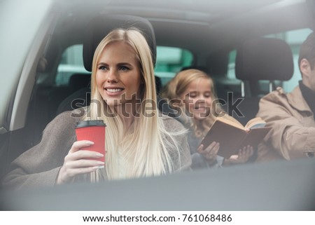 Photo of cheerful young woman sitting in car with her husband and daughter reading book. Looking aside.
