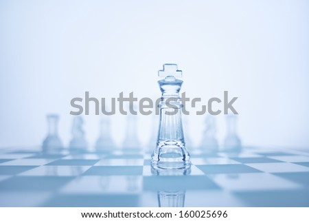 Photo of chess king standing in front of the same colour set in bright background. - stock photo