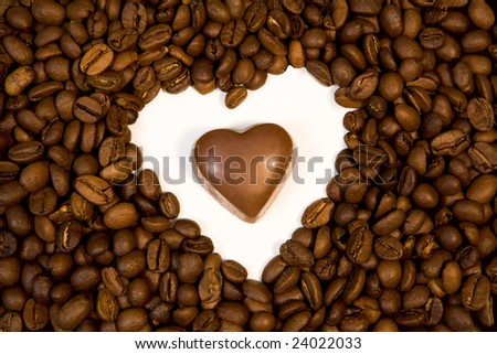 Photo of chocolate candy inside shape of heart made up of coffee beans - stock photo
