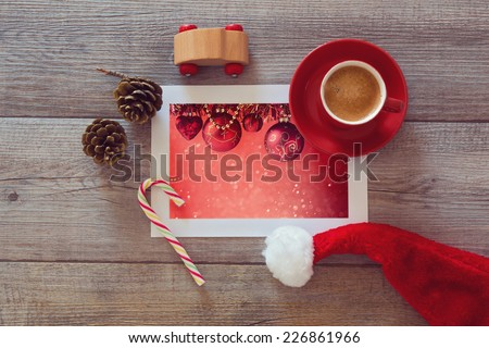 Photo of Christmas holiday decorations on wooden table with coffee cup and Santa hat. View from above - stock photo