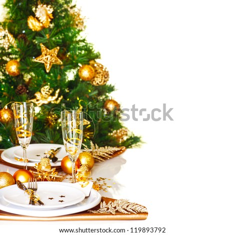 Photo of Christmastime table setting border, beautiful decorated Christmas tree isolated on white background, romantic holiday dinner, luxury white dishware decorated with golden ribbon - stock photo