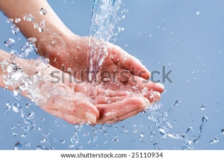 Photo of clean human hands with water splashing on them