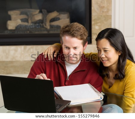 Photo of close mature couple looking at information on the computer screen together with fireplace in background   - stock photo