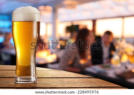 Photo of cold beer glass on the bar table. - stock photo