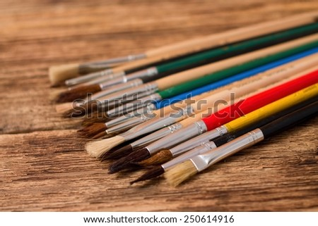 Photo of Collection of different paintbrushes on old worn wooden board all placed in line  - stock photo