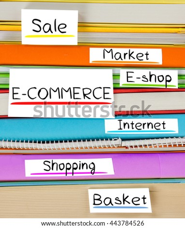 Photo of colorful book stack with bookmarks and labels with E-COMMERCE conceptual words - stock photo