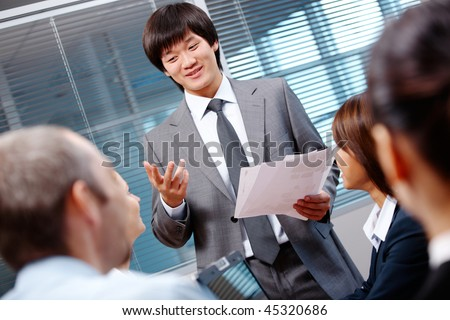 Photo of confident businessman making report to partners at seminar - stock photo