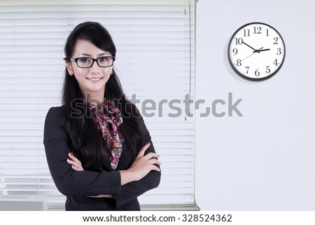 Photo of confident businesswoman standing in the office and smiling at the camera with clock on the wall - stock photo