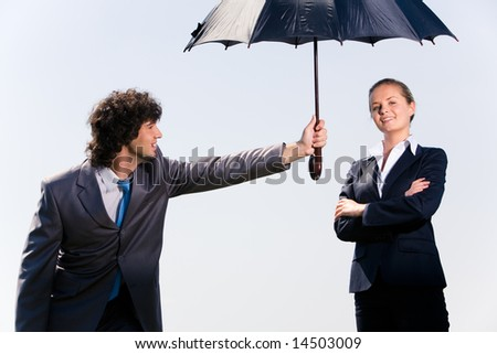 Photo of confident man protecting his coworker by umbrella from rain - stock photo