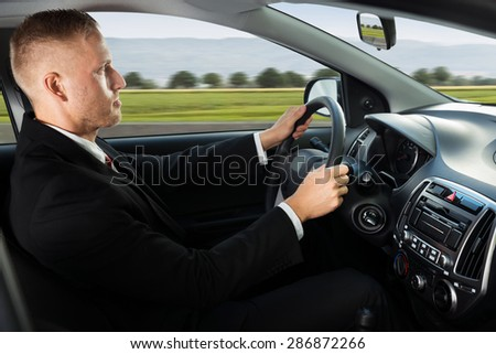 Photo Of Confident Young Businessman Driving His Car - stock photo