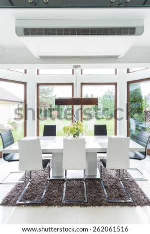 Photo of contemporary stylish main room with big table - stock photo