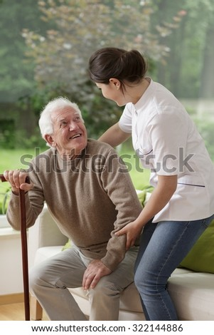 Photo of content old man and his helpful caregiver - stock photo