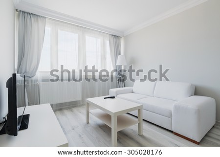 Photo of cosy light living room with simple furniture - stock photo