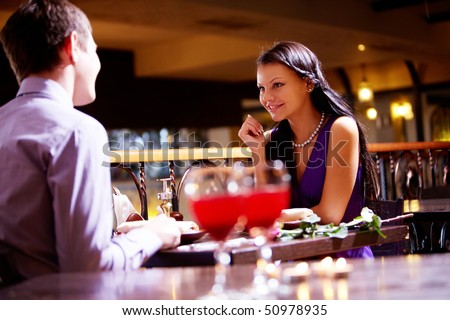 Photo of couple sitting at the table in restaurant - stock photo