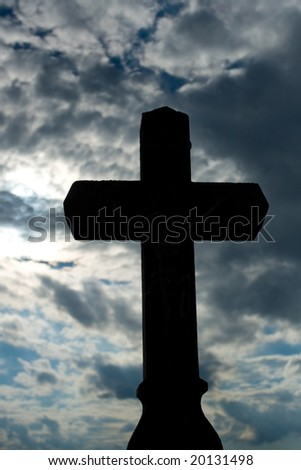 Photo of cross standing at the field whit dull sky on the background