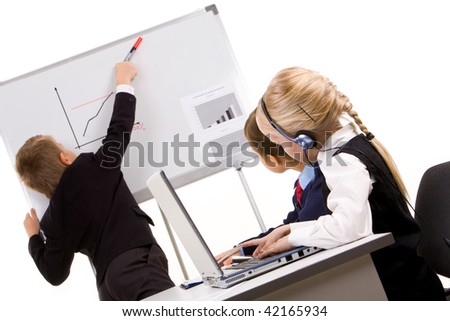 Photo of cute children looking at whiteboard while smart lad presenting project - stock photo
