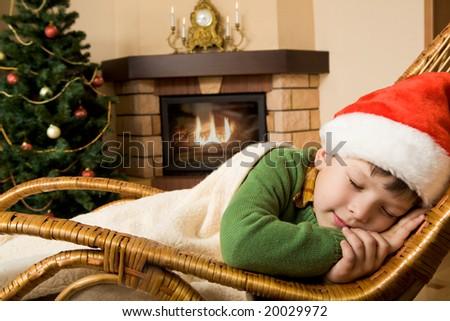 Photo of cute infant wearing santa cap sleeping in rocking chair under blanket - stock photo
