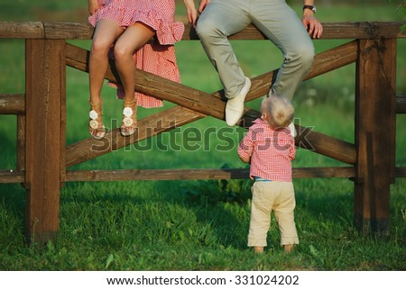 photo of cute little boy with his parents outdoors