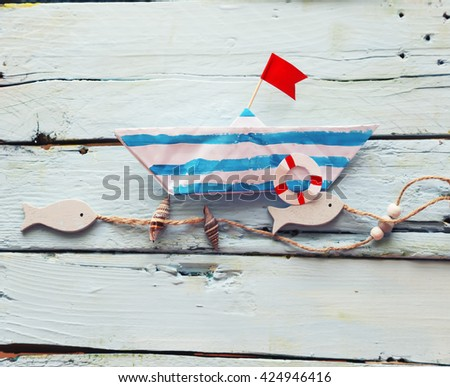 Photo of cute origami paper boat on wooden background - stock photo