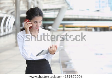 Photo of cute young business woman talking and look at her tablet