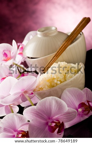 photo of delicious asian rice dish with orchid flowers around - stock photo