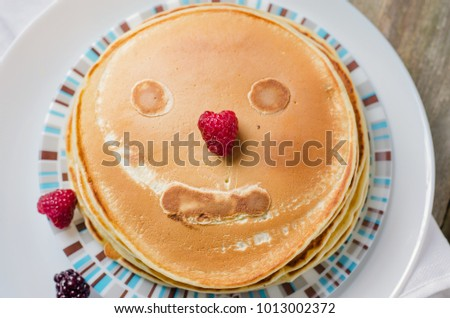 Photo of delicious pancakes with berries and honey over wooden tabe