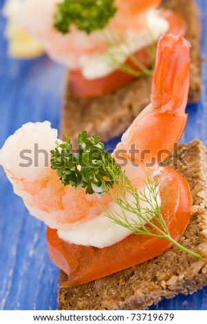 photo of delicious starter made of prawns and tomatoes on black bread