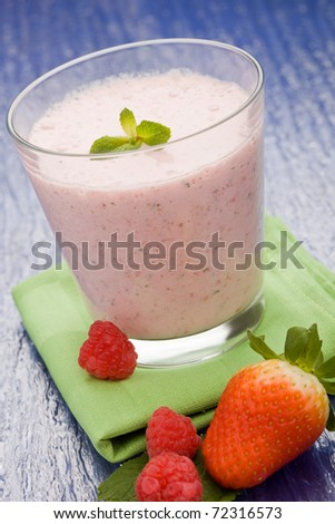 photo of delicious strawberrie milkschake with fruits on green cloth