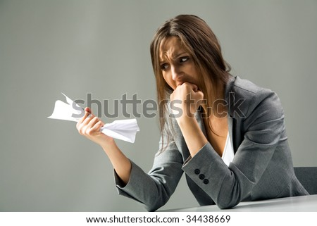 Photo of depressed female with neglected hair looking at paper in her hand and grieving - stock photo