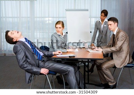 Photo of displeased businesspeople looking sternly at snoring man at presentation - stock photo