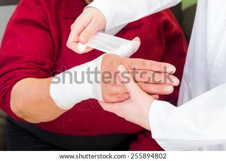 Photo of doctor bandaging the elderly woman thumb - stock photo