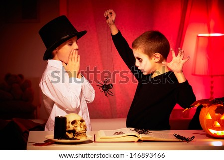 Photo of eerie boy frightening his twin brother with spider on Halloween night - stock photo