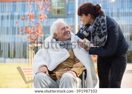 Photo of elderly man and his caring daughter - stock photo