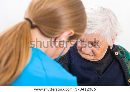 Photo of elderly woman examined by young doctor