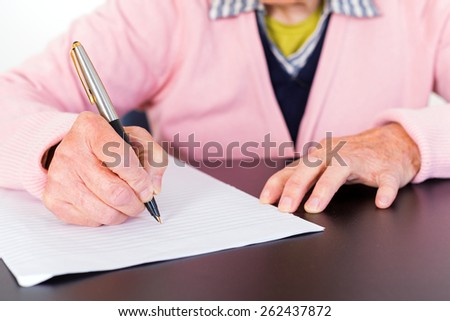 Photo of elderly woman who is writing a letter - stock photo