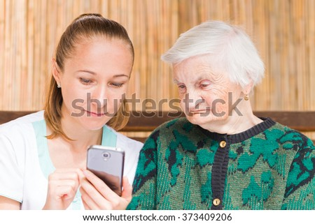 Photo of elderly woman with her caregiver - stock photo