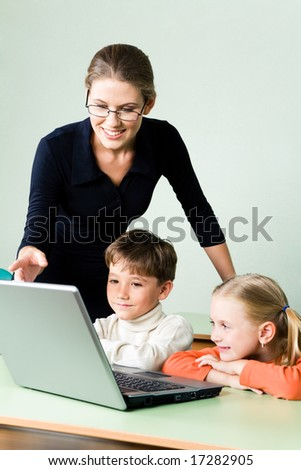 Photo of elegant teacher explaining new topic by pointing at laptop monitor while children looking at it - stock photo