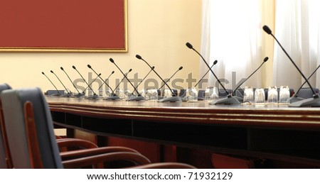 Photo of empty conference room with microphones - stock photo