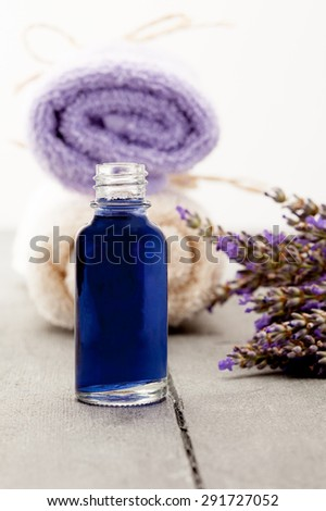 Photo of essential oil with lavender over wooden table