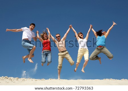 Photo of excited people jumping on sandy beach with their arms raised against blue sky - stock photo