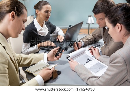 Photo of executive business partners around table interacting with each other - stock photo
