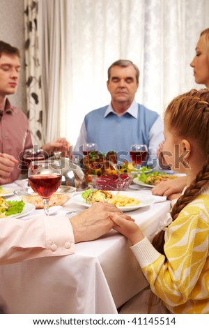 Photo of family members giving thanks to God at festive table while holding each other by hands - stock photo