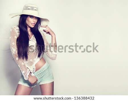 Photo of fashionable brunette woman wearing white hat in sunny day.