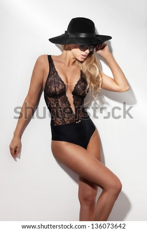 Photo of fashionable sexy blond woman wearing black hat, sunglasses and sensual lace lingerie. - stock photo